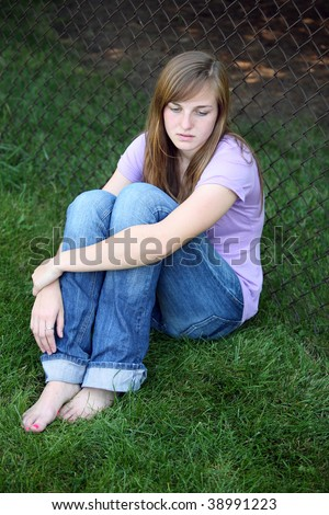 depressed teen girl sitting against fence in grass - stock photo