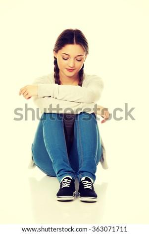 Depressed teen woman sitting. - stock photo