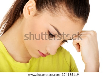 Depressed teen woman touching head.