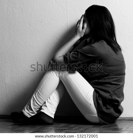 Depressed teenage girl cover the face with her hands. - stock photo