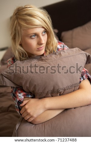 Depressed Teenage Girl Hugging Pillow In Bedroom - stock photo