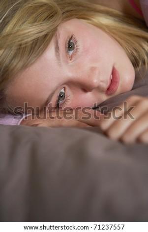 Depressed Teenage Girl Lying In Bedroom - stock photo