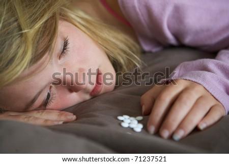 Depressed Teenage Girl Sitting In Bedroom With Pills - stock photo