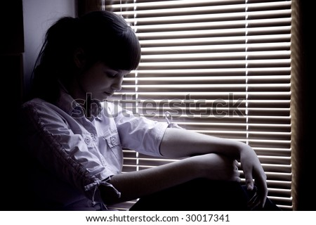 Depressed teenage girl sitting on a window sill - stock photo