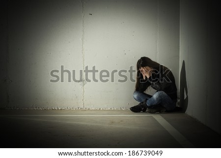 Depressed teenage girl with hands over face sitting in the corner. - stock photo