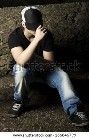 Depressed teenage sitting thinking in the late evening light with his baseball cap pulled low over his eyes - stock photo