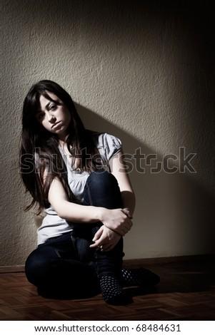 Depressed teenager girl sitting on floor. - stock photo