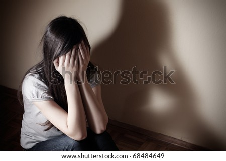 Depressed teenager girl sitting on floor cover face. - stock photo