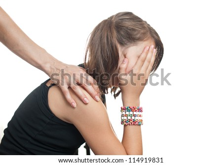 Depressed teenager sitting while hand coming from behind and  offers support.