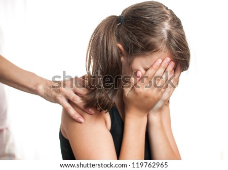 Depressed teenager sitting while hand coming from behind and offers support. - stock photo
