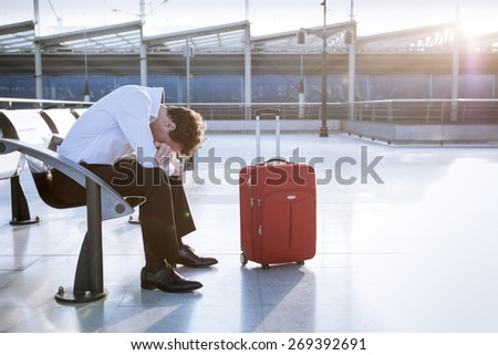 Depressed traveler waiting at airport after flights delays and cancellations - stock photo