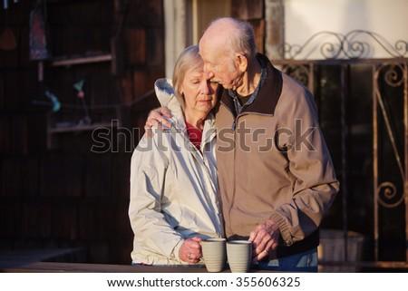 Depressed woman being held by senior man - stock photo