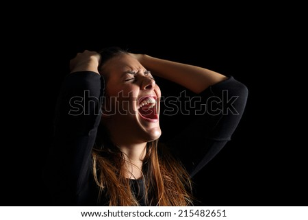 Depressed woman crying and shouting desperately isolated in a black background          - stock photo