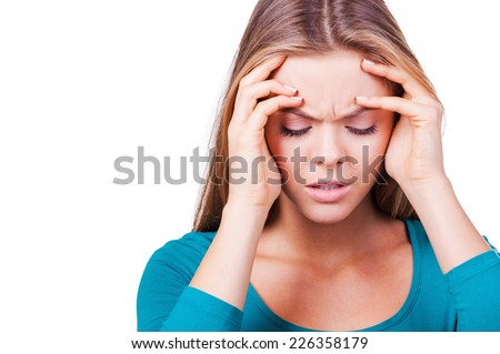 Depressed woman. Depressed young woman touching her head with hands and keeping eyes closed while standing isolated on white