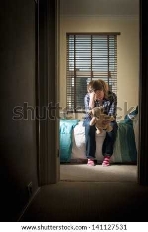 Depressed woman in her bedroom at night - stock photo