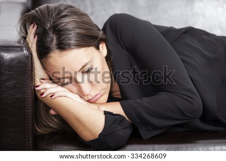 Depressed woman lying on sofa at home - stock photo