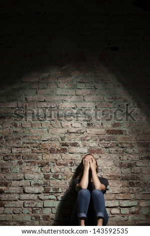Depressed woman sitting alone against brick wall with light coming from above. - stock photo