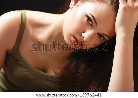 Depressed woman sitting, isolated on black background
