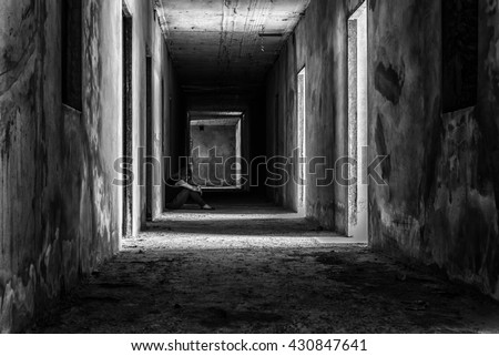 depressed woman sitting on walkway in creepy abandoned building, darkness concept - stock photo