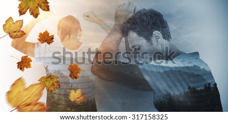 Depressed woman with hands raised against trees and mountain range against cloudy sky - stock photo
