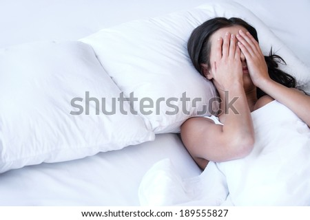Depressed women in bed. Top view of young sad women lying on the bed and hiding her face in hands