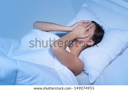 Depressed women in bed. Top view of young sad women lying on the sofa and hiding her face in hands - stock photo