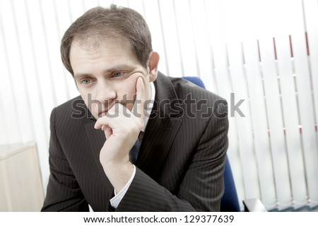 Depressed worried businessman sitting at his desk with his chin in his hand thinking and trying to make difficult decisions - stock photo