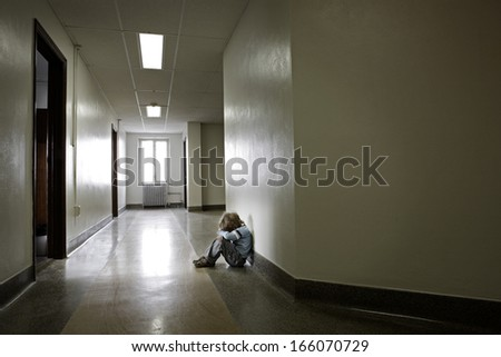 Depressed young boy sitting alone in a hallway - stock photo