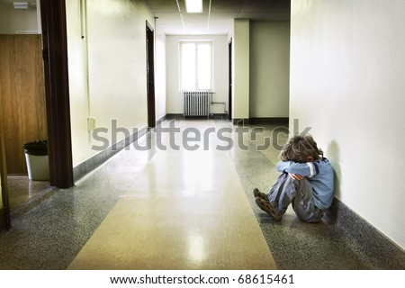 Depressed young boy sitting in the hall - stock photo