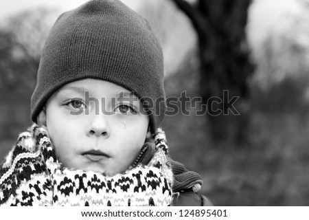 Depressed young boy with tear rolling down cheek - stock photo