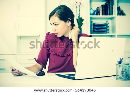 Depressed young brunette sitting at working desk with laptop in office