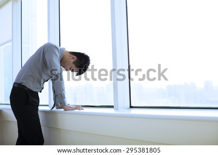 Depressed young business man  in office - stock photo