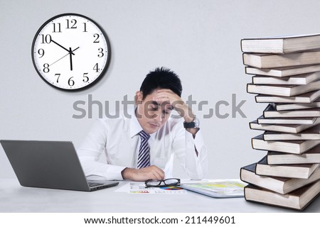 Depressed young businessman holding his head at office - stock photo