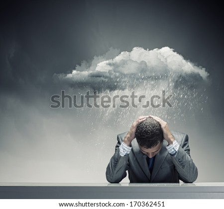 Depressed young businessman sitting wet under rain - stock photo