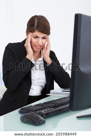 Depressed young businesswoman suffering from headache at computer desk in office - stock photo