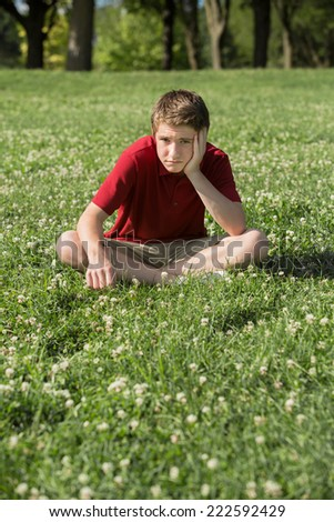 Depressed young Caucasian teen sitting on grass - stock photo