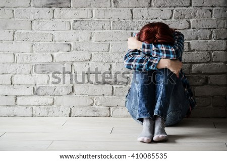 Depressed young crying woman - victim of domestic violence and abuse. Domestic violence