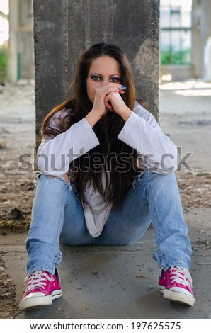 Depressed young girl sitting on the concrete floor of the abandoned building.