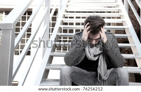 Depressed young guy sitting on the stairs