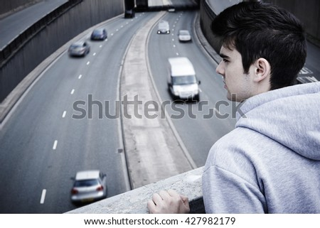 Depressed Young Man Contemplating Suicide On Road Bridge - stock photo
