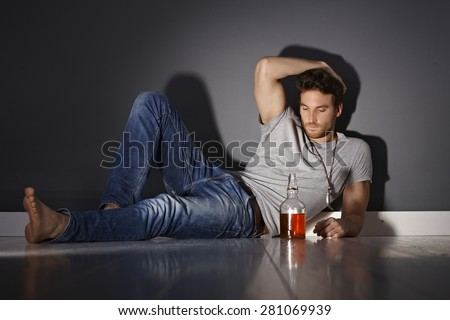 Depressed young man lying on floor, drinking alone. - stock photo