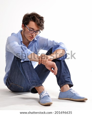 Depressed young man siting down.Frustrated student. - stock photo
