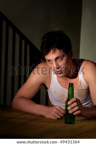 Depressed young man with bottle of beer - stock photo