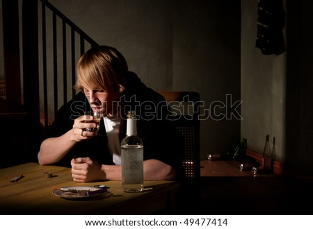 Depressed young man with bottle of clear alcohol - stock photo