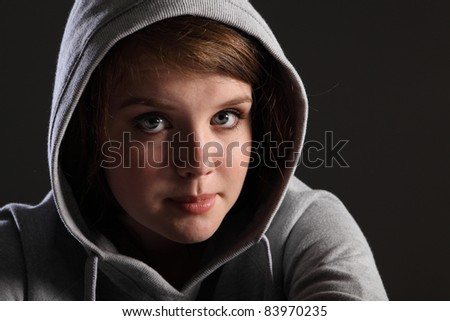 Depressed young teenager girl sitting alone in the dark looking sad, stressed and frightened. She is wearing jeans and a grey hoodie and a worried expression.
