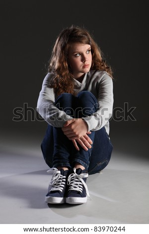 Depressed young teenager girl sitting alone on floor looking sad, stressed and frightened. She is wearing jeans and a grey hoodie and a worried expression.