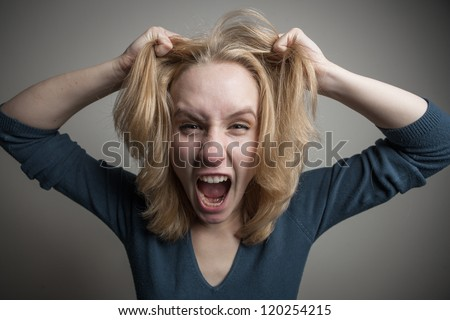 Depressed young woman desperately holding her head and screaming - stock photo