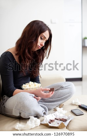 Depressed young woman eating chocolate - stock photo