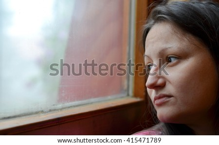Depressed young woman looking out the window