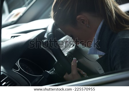 Depressed young woman sitting in a car leaning to steering wheel.